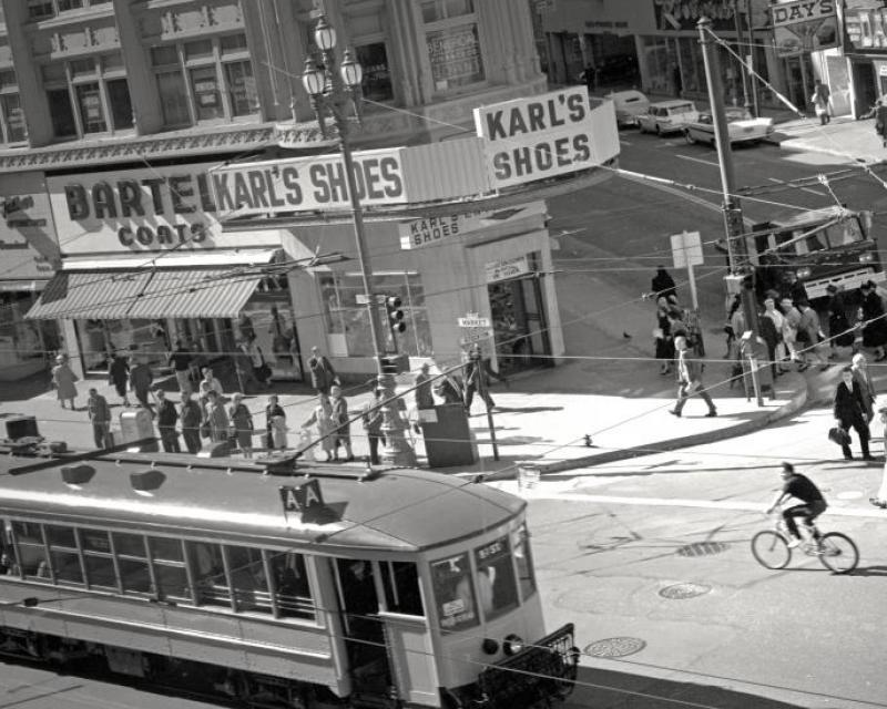 Historic image of trolley card, people walking along city street