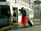 A woman stands dramatically posed outside the N Judah train line.