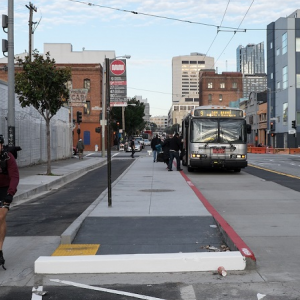 A man rides in a bike lane between the sidewalk and a concrete island where people board a Muni bus on 11th at Harrison.