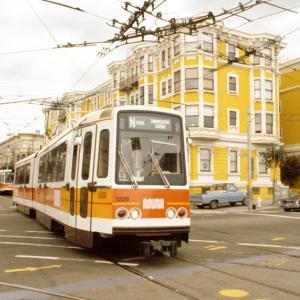A Muni light rail vehicle with orange stripes and Muni worm logo crosses Church Street at Duboce in front of a yellow building.