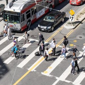 A bustling crosswalk, cars and Muni buses at Mission and 4th streets.
