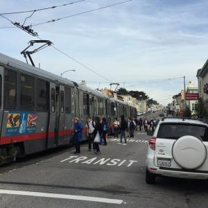 People on Taraval Street board a stopped Muni train