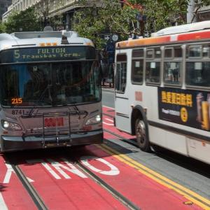 Muni buses drive down red-colored transit-only lanes on Market Street.