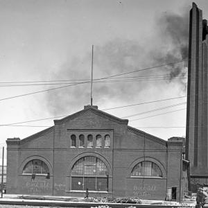 Black and white photo taken in June, 1906 of a large brick building on Market and Valencia Streets. The building is partially damaged with the top of a tall smokestack broken off and light black smoke coming out of it.  Surrounding the building are piles of rubble from destroyed and damaged buildings.