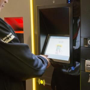 A man uses a touch screen for the new parking garage payment system.