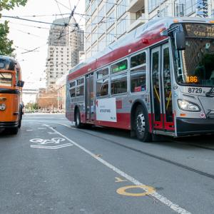 Two Muni buses on Steuart street. A 1938 orange and black painted White brand and a new 2013 red and grey New Flyer bus.