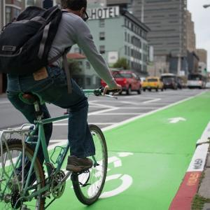 A man bikes on a parking-protected bike lane on 7th Street.