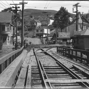 View north on Diamond near Chenery of wooden bridge and streetcar rails, street curving uphill and early 20th century buildings