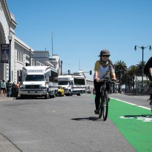 A person bicycling towards the camera in the green bike lane on the Embarcadero's roadway