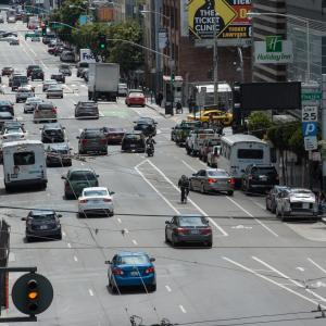 Vehicles travel southbound in three travel lanes on 8th Street. A cyclist navigates around vehicles in the buffered bike lane.