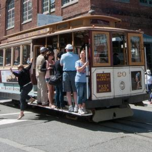 cable car with people on board stopped in intersection to unload