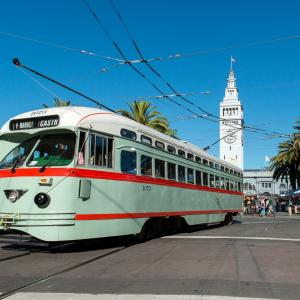 mint green streetcar with red striping and white roof in front of Ferry building on Market Street