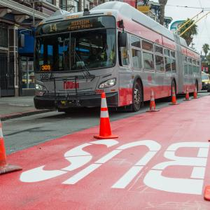 bus driving by red transit lane work on mission street