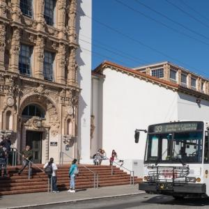 image of White and orange Muni trolley bus sits in front of Mission High School while students mingle