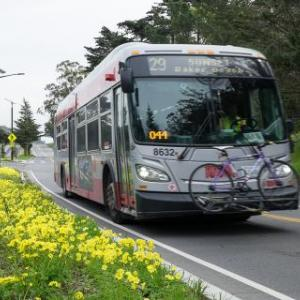 Hybrid bus rides through city street