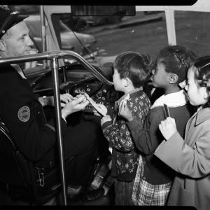 Bus driver greets children in historic photo