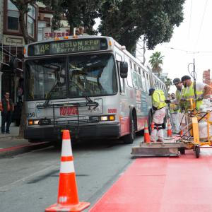 Crew placing red transit only lanes next to a 14R bus