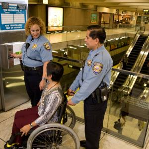 Image of two Muni safety officers helping a woman in a wheelchair into an elevator