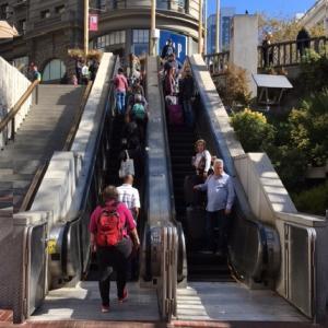 Image of people coming down a muni metro escalator at Hallidie Plaza