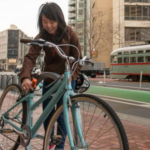 Image of a woman locking her bike on Market Street