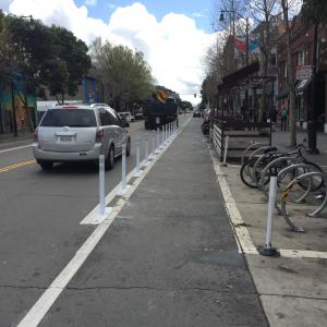 New paint and flext post on Valencia Street in front of a parklet and bike corral