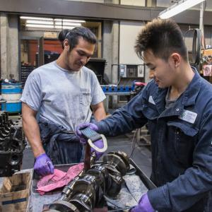 Image of 2 apprentices with engine crankshaft
