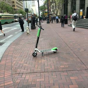 A Lime scooter parked on a Market St. sidewalk