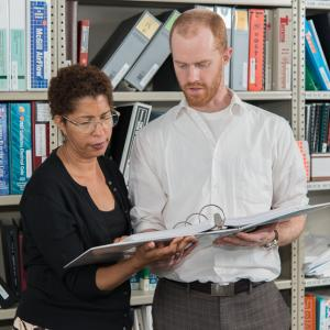 two people reading bound report in library-type room