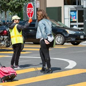 People crossing the street with the help of a crossing guard.