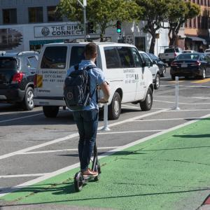 Man rides shared, powered scooter in bike lane