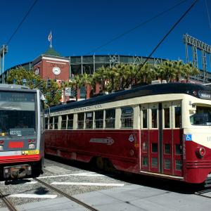 a rail train and a street car pass AT&T park