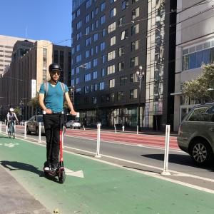 A person wearing a helmet rides a scooter in a bike lane