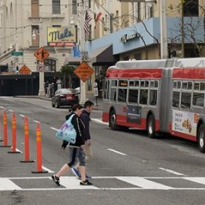 People crossing Van Ness at a crosswalk