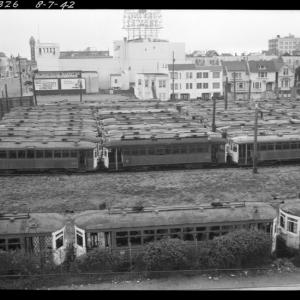 derelict streetcars sit in a large empty lot