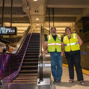 SFMTA staff standing in front of the escalator at Van Ness Station