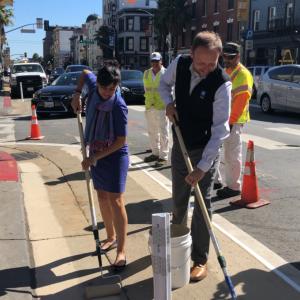 Tom Maguire and Viktoriya Wise painting sidewalk zones.