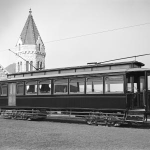 Funeral streetcar at cemetery with stone building in background