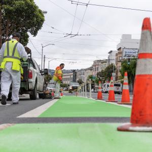 crews installing green bike paths