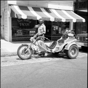 "Vintage black and white photo of a person standing over a motorcycle in front of a restaurant ""Noe Valley Tacos"""