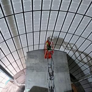 A worker installs decorative panels in a future Central Subway Station.