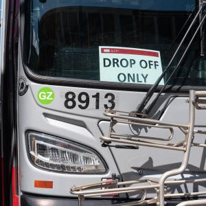 "A Muni bus with a ""Drop Off Only"" sign."