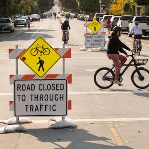 "Image of temporary barriers in the travel lane stating ""road closed to through traffic"" with three bicyclists using the street"