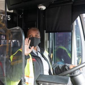 Photo of Muni operator behind the wheel, wearing a mask