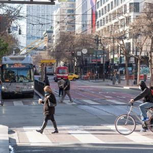 Photo of Market Street intersection with 5 Fulton bus, pedestrians, people on bicycles, a taxi, an ambulance, bikshare station,