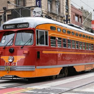 red and orange streetcar running on F Line along Market Street