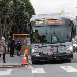 """Passengers board a 38R Geary Rapid in the Richmond District with the help of a temporary wooden """"bus bulb."""""""