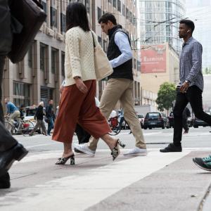 Pedestrians crossing 1st Street at Market Street