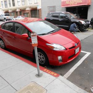 A shared vehicle parked at a permitted car share only curbside parking space.