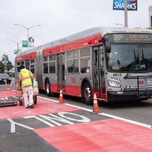 Photo of crew striping red paint on Geary Boulevard