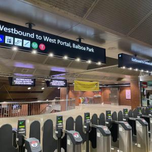 Photo of subway station fare gates with new overhead wayfinding signs depicting east, west directions and destinations for train